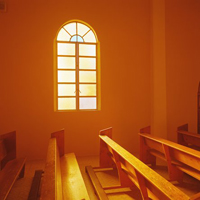 Pews lit by sunlight coming through a Church window.